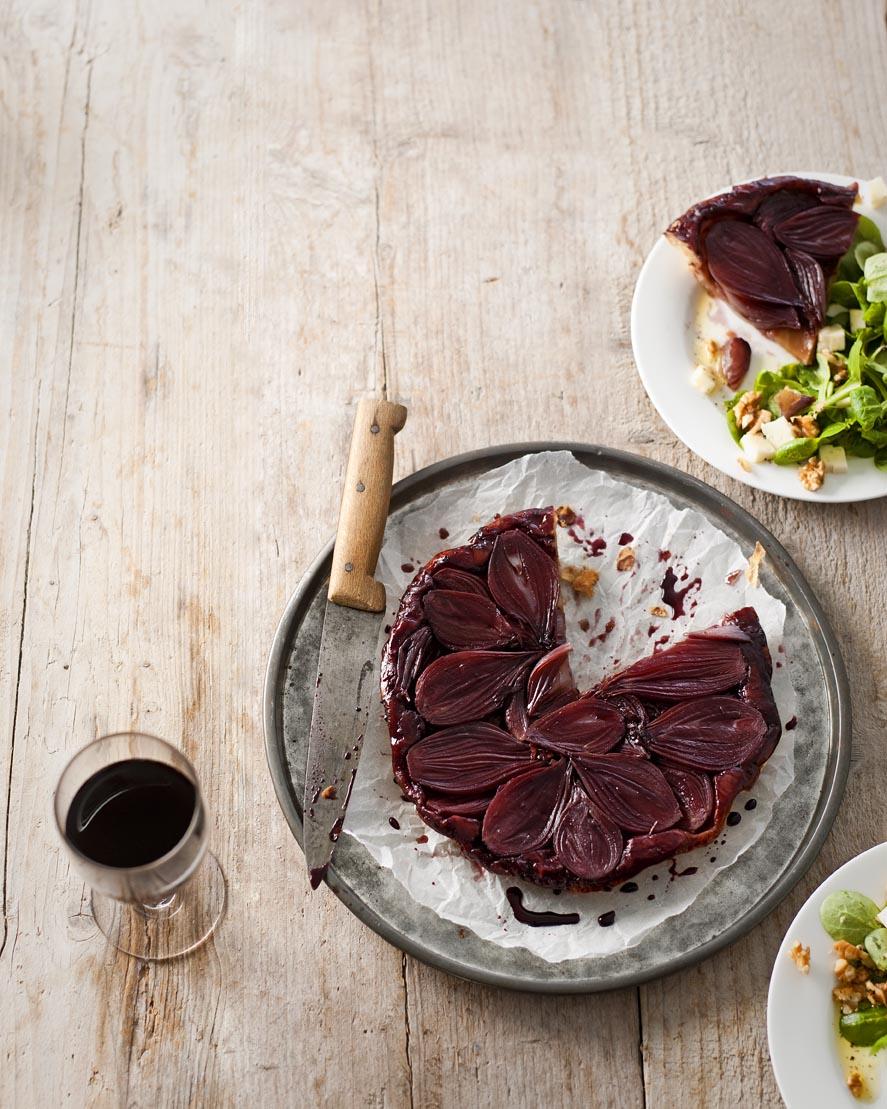 Verlang je vaak naar de eenvoud van de Franse bistro? Janneke Philippi laat je in het Parijse nummer van delicious. zien hoe je thuis superlekker en toch simpel Frans kookt. Maak haar tarte-tatin met sjalotjes bijvoorbeeld eens. tarte tatin met sjalotjes hoofdgerecht | 4 personen 50 g rietsuiker 150 ml rode wijn, bijv. merlot 5 plakjes bladerdeeg, ontdooid 1 netje sjalotten* (500 g), gehalveerd 1 ei, losgeklopt 150 g veldsla 150 g Franse kaas (bijv. roombrie, zachte geitenkaas, chaumes of port salut), in blokjes 100 g walnoten, grof gebroken 4 el olijfolie extra vierge ook nodig: dichte taartvorm met gladde iets hogere (3-4 cm) wand van 24-26 cm Ø ingevet Kook de suiker en wijn tot de helft in en tot het siropig wordt. Neem de wijnsiroop van het vuur.** Verwarm intussen de oven voor op 200°C. Leg de plakjes deeg op elkaar en laat elk lapje steeds iets verspringen, zo rolt het makkelijker uit tot een ronde lap. Rol het deeg uit tot een lap van 30 cm Ø. Schenk de wijnsiroop in de vorm en draai de vorm zodat de hele bodem met siroop is bedekt. Leg de sjalotten op het snijvlak dicht tegen elkaar aan in de siroop. Leg de deeglap over de sjalotten en vouw het overhangende deeg naar binnen toe weg, tussen de rand van de vorm en de sjalotten in. Bestrijk het deeg met ei en prik met de punt van een scherp mes enkele keren in het deeg. Bak de tarte tatin in de oven in 25-30 min. goudbruin en gaar. Was en droog intussen de veldsla. Mocht je nog een sjalotje over hebben, snijd het fijn en meng met de kaas en de noten door de salade. Maak de salade aan met olijfolie en zout en peper. Neem de tarte tatin uit de oven. Leg een schaal erop en keer ze samen, pas op er kan wat hete siroop uitlekken. Snijd de sjalottentaart aan tafel in punten en serveer met de salade. Bereiden ± 25 min. / oven ± 30 min. RECEPTEN JANNEKE PHILIPPI FOTOGRAFIE JEROEN VAN DER SPEK STYLING JET KRINGS FOODSTYLING BART STUART PRODUCTIE TRUDELIES SCHOUTEN * Sjalotten eten we te weinig, uien trouwens ook. Jamme